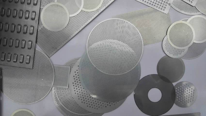 There are many kinds of perforated filter discs on the grey background.