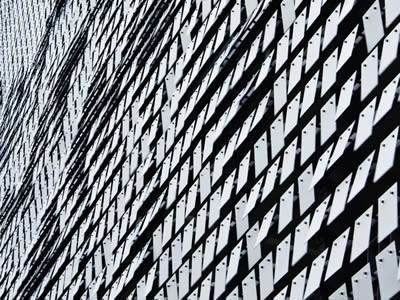 Many perforated kinetic plates are covering a building.