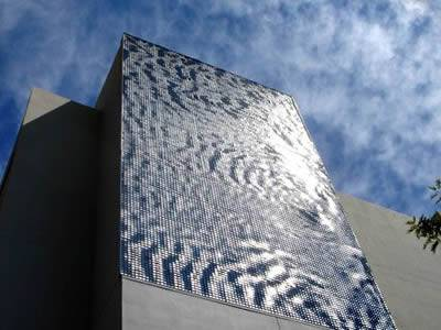 A perforated kinetic facade covered building is under a blue sky.